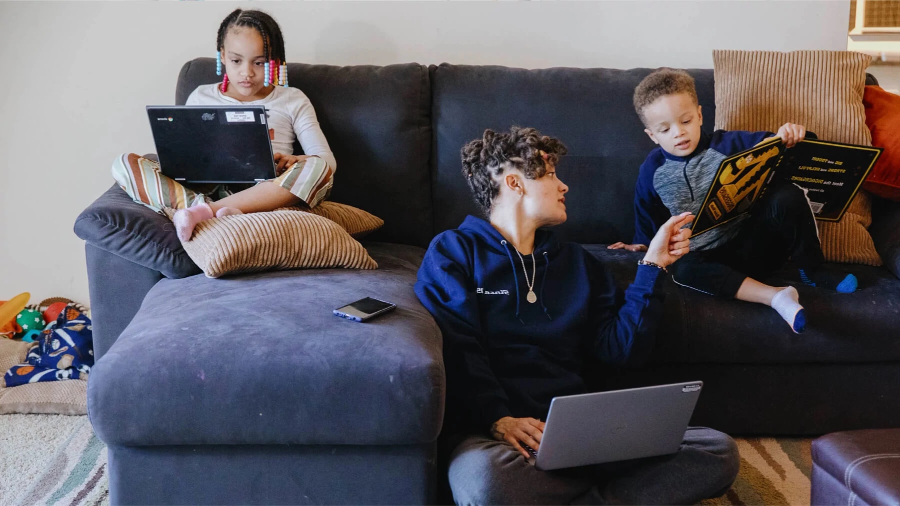 photo of a woman with two young children reading on a large blue sofa