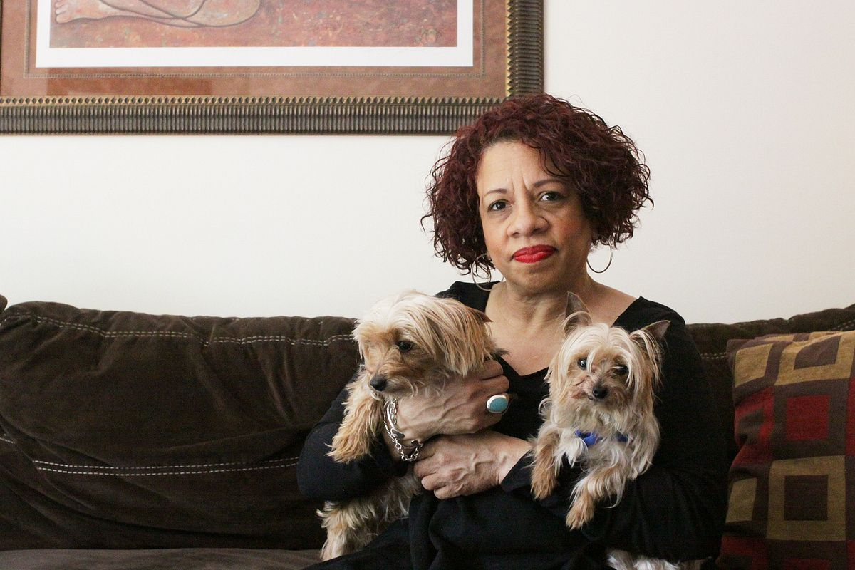 older black woman on her couch holding two small dogs