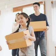 a family smiling and moving in with boxes